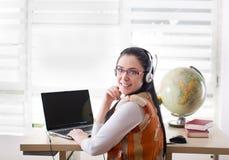 Ragazza dello studente con il computer portatile e i heaphones Immagine Stock