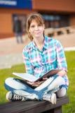 Ragazza dello studente con il quaderno sul banco Città universitaria di estate Immagine Stock
