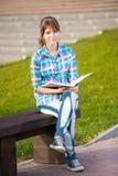 Ragazza dello studente con il quaderno sul banco Città universitaria di estate Fotografia Stock Libera da Diritti