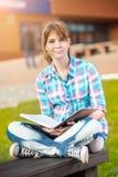 Ragazza dello studente con il quaderno sul banco Città universitaria di estate Immagini Stock