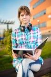 Ragazza dello studente con il quaderno sul banco Città universitaria di estate Immagine Stock Libera da Diritti