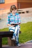 Ragazza dello studente con il quaderno sul banco Città universitaria di estate Immagini Stock Libere da Diritti