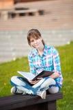 Ragazza dello studente con il quaderno sul banco Parco della città universitaria di estate Fotografie Stock