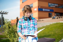 Ragazza dello studente con il quaderno sul banco Parco della città universitaria di estate Fotografie Stock Libere da Diritti