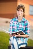 Ragazza dello studente con il quaderno sul banco Parco della città universitaria di estate Immagine Stock