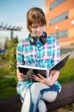 Ragazza dello studente con il quaderno sul banco Parco della città universitaria di estate Fotografia Stock