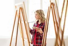 Ragazza dello studente con la pittura del cavalletto alla scuola di arte Fotografia Stock