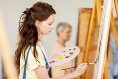 Ragazza dello studente con la pittura del cavalletto alla scuola di arte Fotografia Stock Libera da Diritti