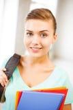 Ragazza dello studente con le cartelle della borsa e di colore di scuola Fotografie Stock