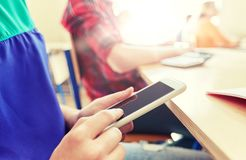 Ragazza dello studente con lo smartphone che manda un sms alla scuola Fotografia Stock