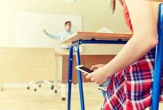 Ragazza dello studente con lo smartphone che manda un sms alla scuola Immagini Stock Libere da Diritti