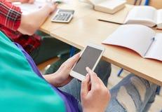 Ragazza dello studente con lo smartphone che manda un sms alla scuola Immagine Stock
