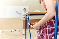Ragazza dello studente con lo smartphone che manda un sms alla scuola Immagine Stock Libera da Diritti