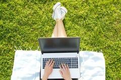 Ragazza dello studente di college che si siede sul prato inglese verde che fa compito sul suo computer portatile Giovane donna ch Fotografie Stock Libere da Diritti