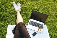 Ragazza dello studente di college che si siede sul prato inglese verde che fa compito sul suo computer portatile Giovane donna ch Fotografie Stock