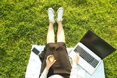 Ragazza dello studente di college che si siede sul prato inglese verde che fa compito sul suo computer portatile Giovane donna ch Immagini Stock