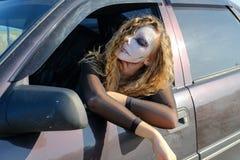 Ragazza dello zombie con gli occhi neri e bocca sanguinosa nell'automobile immagine stock libera da diritti