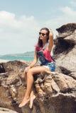 Ragazza in denim complessivo sulla spiaggia della roccia Fotografia Stock