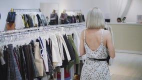 Ragazza di acquisto Ritratto di bella donna nel deposito dei vestiti Ragazza bionda felice con le labbra rosse in un negozio di v video d archivio