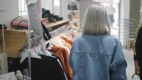 Ragazza di acquisto Ritratto di bella donna nel deposito dei vestiti Giovane ragazza bionda con le labbra rosse in un negozio di  stock footage