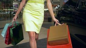 Ragazza di acquisto in vestito giallo con i pacchetti con gli acquisti che cammina accanto ad un'automobile in centro commerciale video d archivio