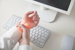 Ragazza di affari con dolore sul lavoro del polso in computer Sindrome dell'ufficio immagine stock libera da diritti