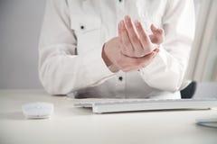 Ragazza di affari con dolore sul lavoro del polso in computer Sindrome dell'ufficio immagini stock libere da diritti