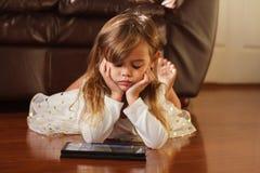 Ragazza di 4 anni dolce nel bianco, giocante con il iPad Fotografia Stock