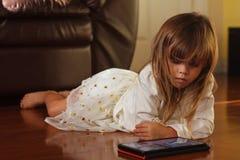 Ragazza di 4 anni dolce nel bianco, giocante con il iPad Immagine Stock Libera da Diritti