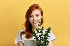 Ragazza di Aweome con un fiore sulle sue mani che posano alla macchina fotografica immagine stock libera da diritti