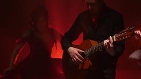 Ragazza di ballo di flamenco in una musica di gioco vicina dei chitarristi del fondo del fumo Luce da dietro Fumi la priorità bas stock footage
