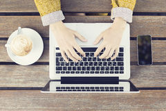 Ragazza di battitura a macchina con il computer portatile, lo smartphone e la tazza da caffè sulla linguetta di legno Fotografie Stock
