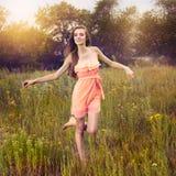 Ragazza di bellezza all'aperto che gode della natura e del funzionamento sul prato Fotografie Stock Libere da Diritti