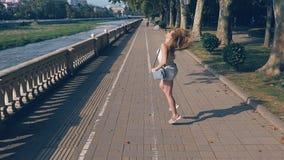 Ragazza di bellezza che gode della natura Correndo e saltare sulla via lungo il lungomare Bello divertiresi della giovane donna stock footage