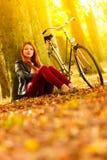 Ragazza di bellezza che si rilassa nel parco di autunno con la bicicletta, all'aperto Fotografia Stock Libera da Diritti