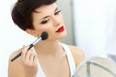 Ragazza di bellezza con la spazzola di trucco. Naturale compensi la donna castana con le labbra rosse.