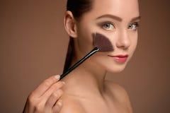 Ragazza di bellezza con la spazzola di trucco Pelle perfetta Applicazione del trucco Immagini Stock