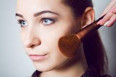 Ragazza di bellezza con le spazzole di trucco Naturale compensi la donna castana con gli occhi del bleu Bello fronte makeover Pel Fotografie Stock Libere da Diritti