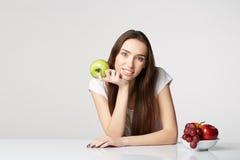 Ragazza di bellezza della donna con i frutti e mela dell'uva sul fondo di bianco grigio Fotografia Stock