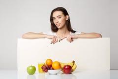 Ragazza di bellezza della donna con il canestro di frutti sul fondo di bianco grigio Fotografia Stock