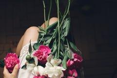 Ragazza di Boho in vestito bianco della Boemia che tiene le belle peonie rosa sulle gambe, vista superiore Spazio per testo donna fotografia stock