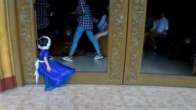 Ragazza di fiore sveglia in vestito blu divertendosi al gradino della porta della chiesa stock footage