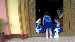 Ragazza di fiore sveglia in vestito blu divertendosi al gradino della porta della chiesa video d archivio