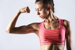 Ragazza di forma fisica che mostra i muscoli del bicipite immagini stock
