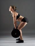 Ragazza di forma fisica con il bilanciere che fa deadlift Fotografia Stock