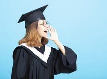 Ragazza di graduazione che urla con il gesto fotografia stock