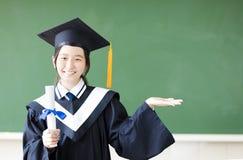Ragazza di graduazione con la mostra del gesto nell'aula Fotografia Stock Libera da Diritti