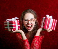 Ragazza di grido felice in vestito rosso con due contenitori di regalo Fotografia Stock