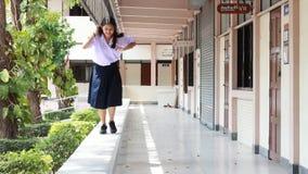 Ragazza di High School dello studente tailandese la bella si rilassa e giocando a scuola stock footage
