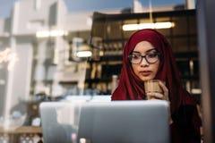 Ragazza di Hijab con caffè facendo uso del computer portatile al caffè fotografie stock libere da diritti